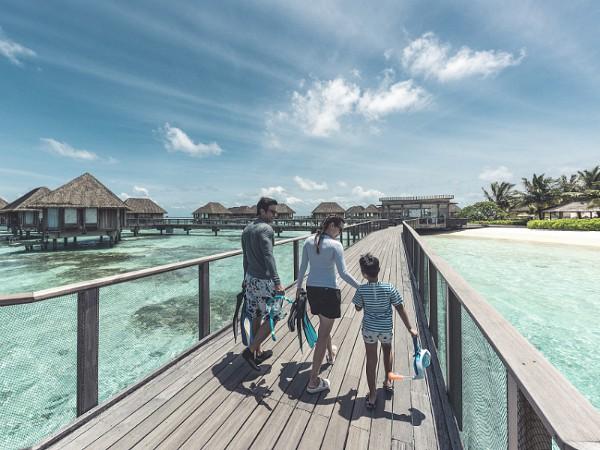 gezin wandelt over de steiger op tropisch strand