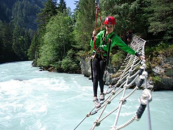een kind klautert over touwbrug over rivier