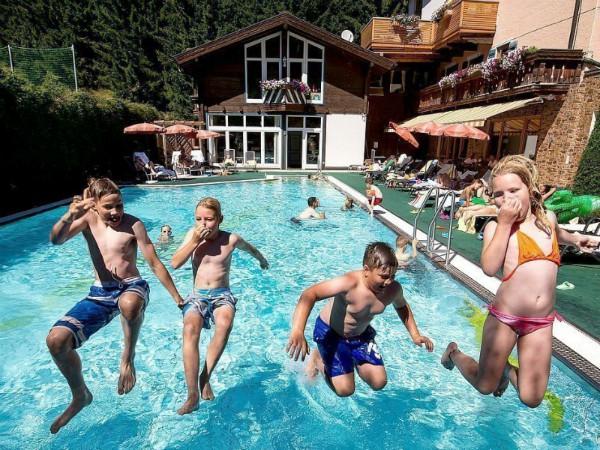 kinderen springen in het zwembad van hotel filzmooserhof