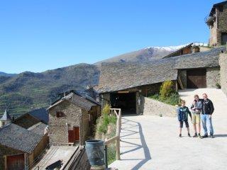 De parkeerplaats van Casa Bellera met dorp en bergen op de achtergrond