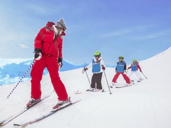 kinderen skieën achter de skilerares aan