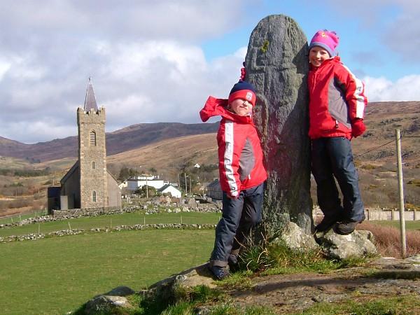 Kinderen poseren bij een religieuze steen in Glencolmcille, Donegal