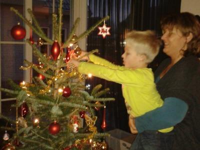 Tycho hangt de kerstballen in de boom