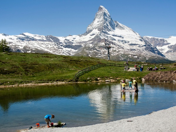 Kinderen spelen bij een meertje bij Zermatt