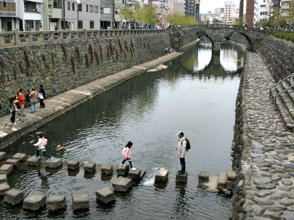 Kinderen spelen bij de oudste brug van Nagasaki