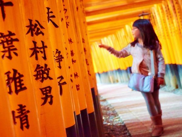 Meisje telt de Torii gates in de beroemde Torii galerij in Kyoto