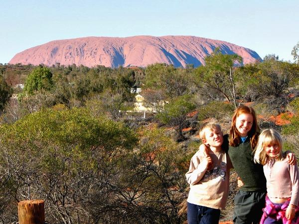 De kinderen poseren voor Uluru, oftewel Ayers Rock