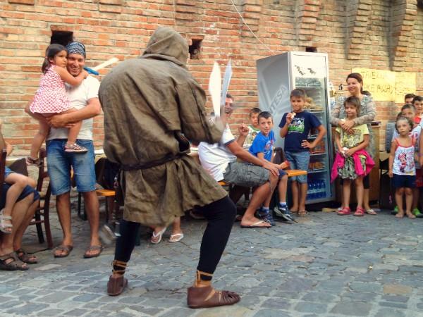 Een acteur vermaakt de kinderen in kasteel Gradara
