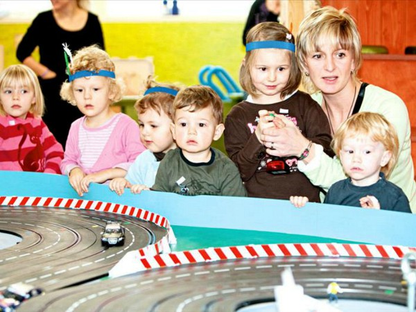 kinderen kijken naar een racebaan bij de kinderclub