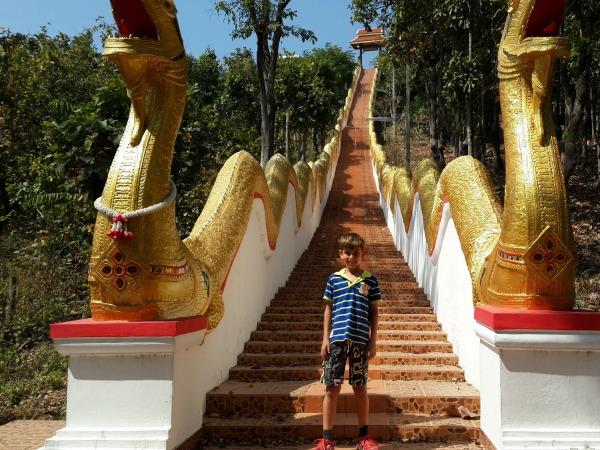 Poseren bij de trap naar een tempel in Noord-Thailand