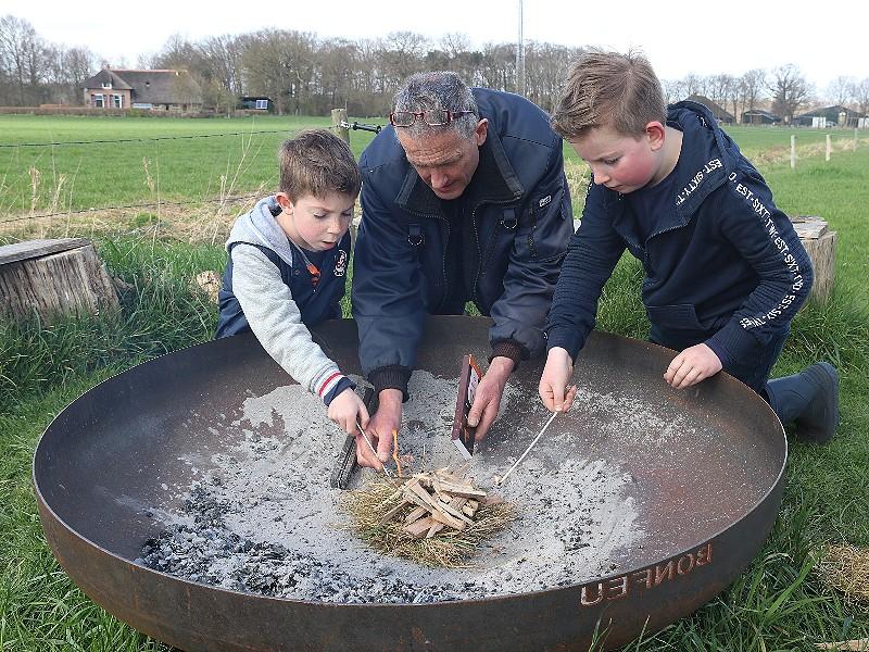 Samen met papa een vuurtje maken.