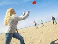 Meisje vangt frisbee op het strand