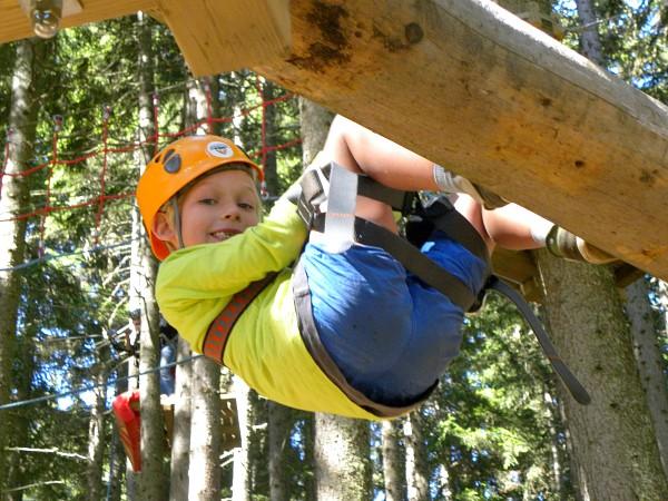Jongen in het klimpark hangend aan de zijkant van een boomstam