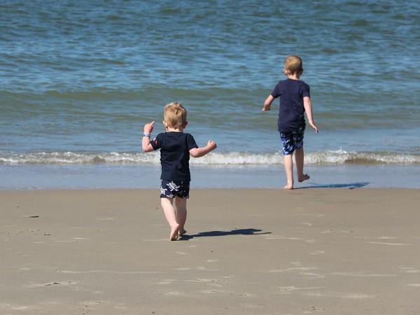 kinderen rennen over strand naar het water