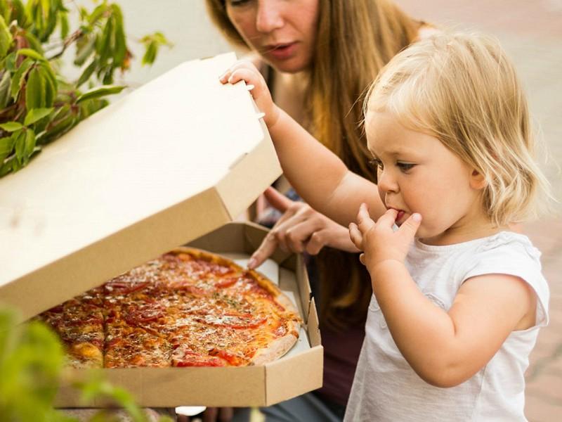 meisje snoept van pizza
