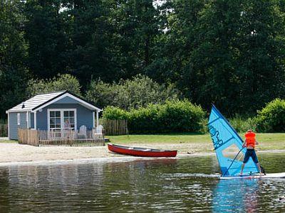 vakantiehuisje aan het water met surfer