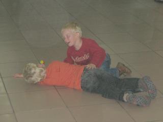 De jongens spelen op de grond voor de douane