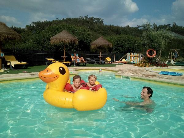 kinderen vermaken zich op de opblaas eend in het zwembad