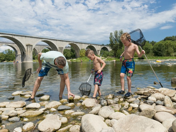 Vader en zoons zoeken stenen in de rivier
