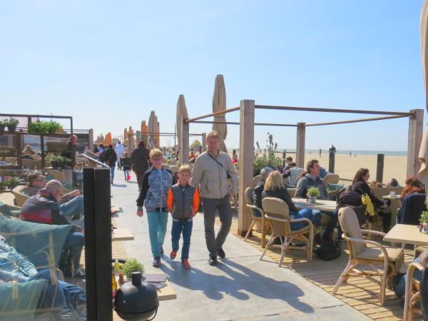 Vader en zoons wandelen langs het strand en terrasjes in Scheveningen
