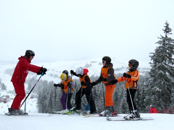 De skileraar doet het voor