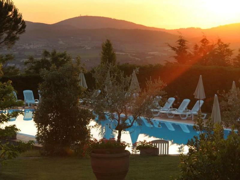 Zonsondergang bij zwembad met uitzicht in Toscane
