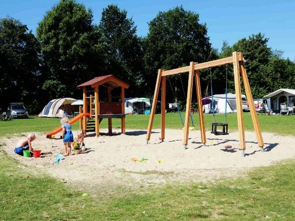 Campingplekken rond een speelveld met speeltuin