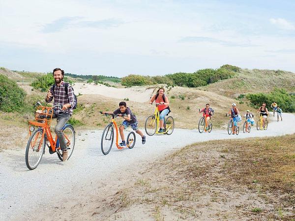 Gezin rijdt op de fiets en step door de duinen