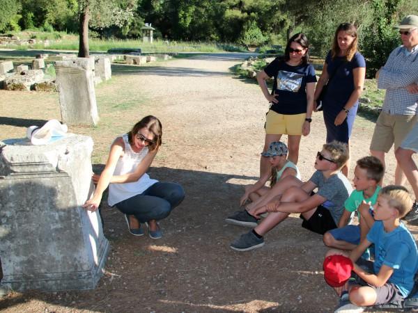 De kinderen krijgen uitleg van onze gids bij de ruïnes van Olympia