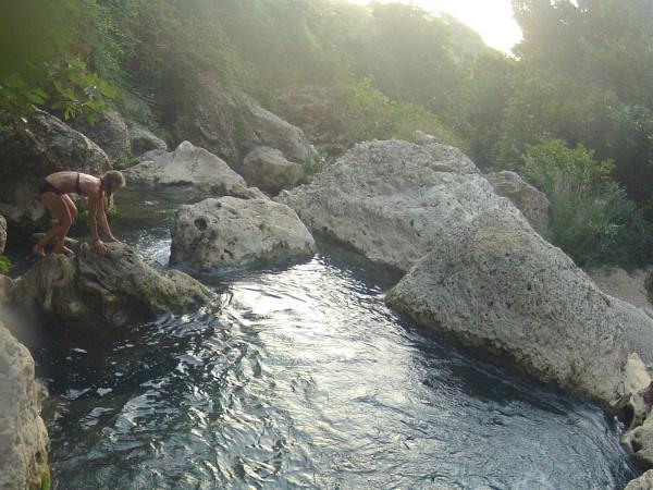meisje klimt over de rotsen in de rivier