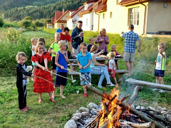 Kinderen roosteren marshmallows bij het kampvuur