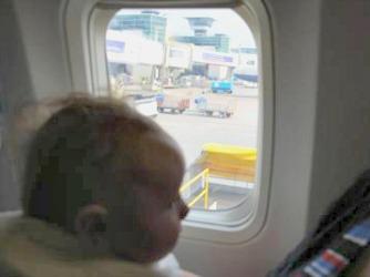 Een baby kijkt uit het vliegtuigraam