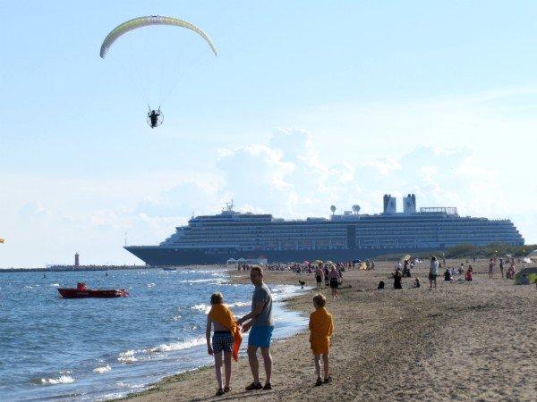 Op het strand langs de Venetiaanse kust zie je de cruiseschepen langsvaren