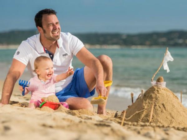 Baby met papa op het strand