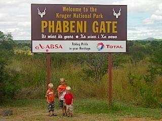 De jongens voor het welkom bord van Kruger